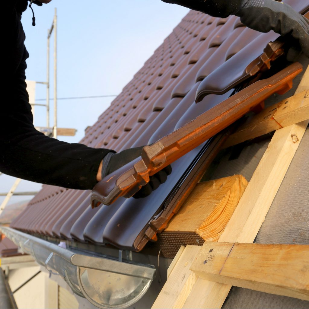 Putting tiles on a roof.
