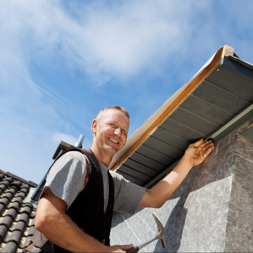 roofer smiling while performing a roof repair