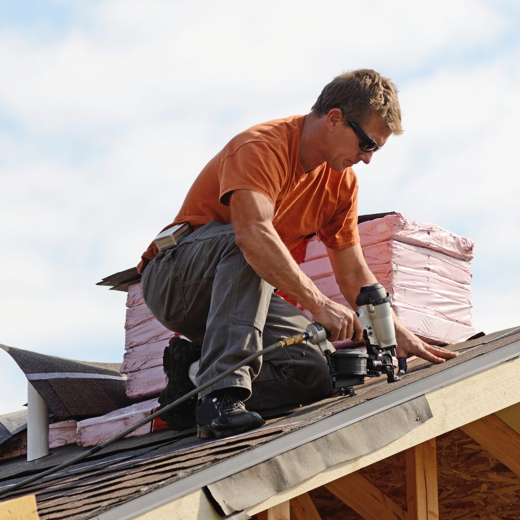 Roofing contractor attaching shingles