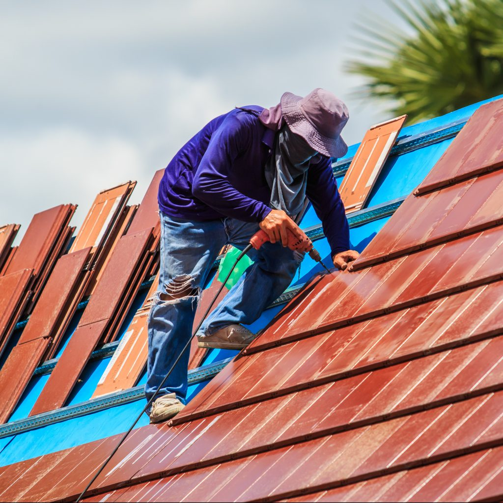 Roofer applying shingles.