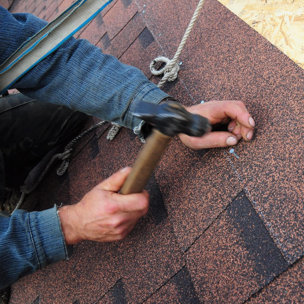 Roofer nailing down shingles.